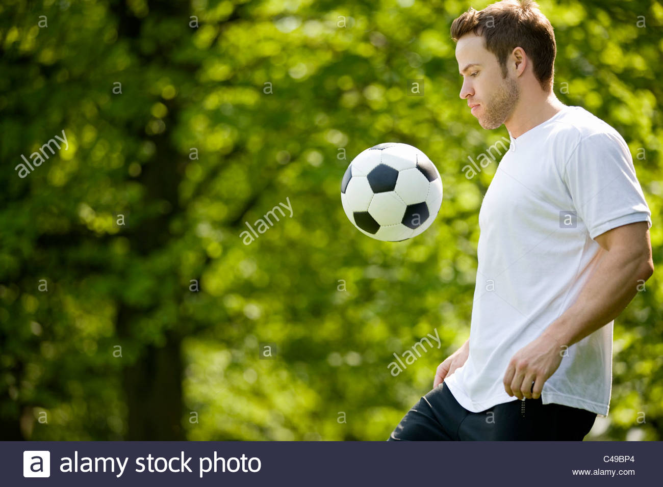 A young man playing with a football - Stock Image