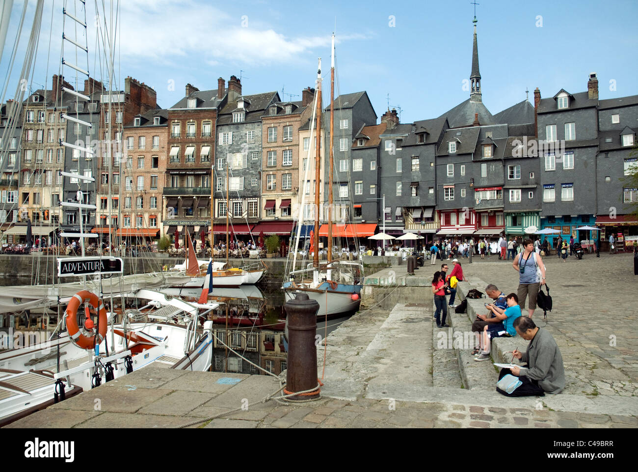The broad quayside beside Honfleur's Vieux Bassin, old port, as in past times attracts artists and travellers - Stock Image