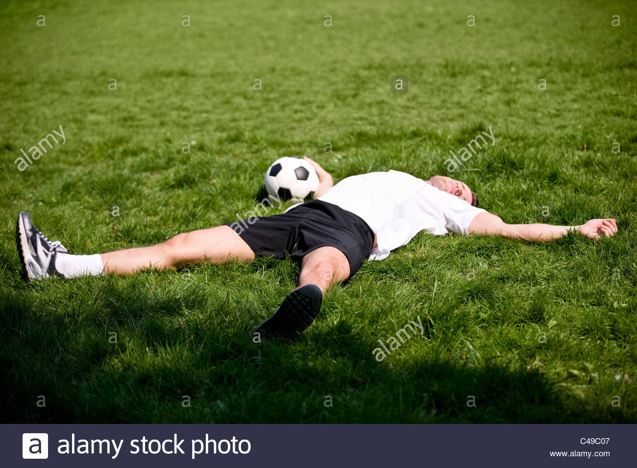 A young man lying on the grass, holding a football - Stock Image
