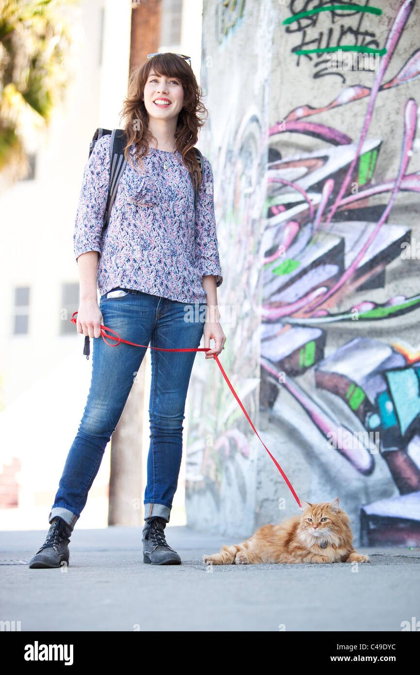 A smiling young woman with a longhaired orange Manx cat on a leash, standing in an urban area with graffiti. - Stock Image