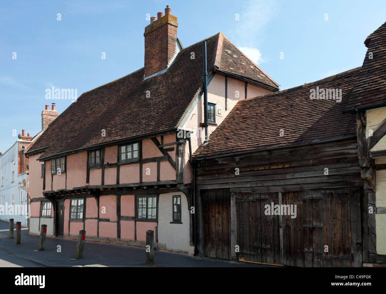 Old House dwelling Titchfield Hampshire England UK High Street timber frame wood wooden pink weathered oak garage - Stock Image