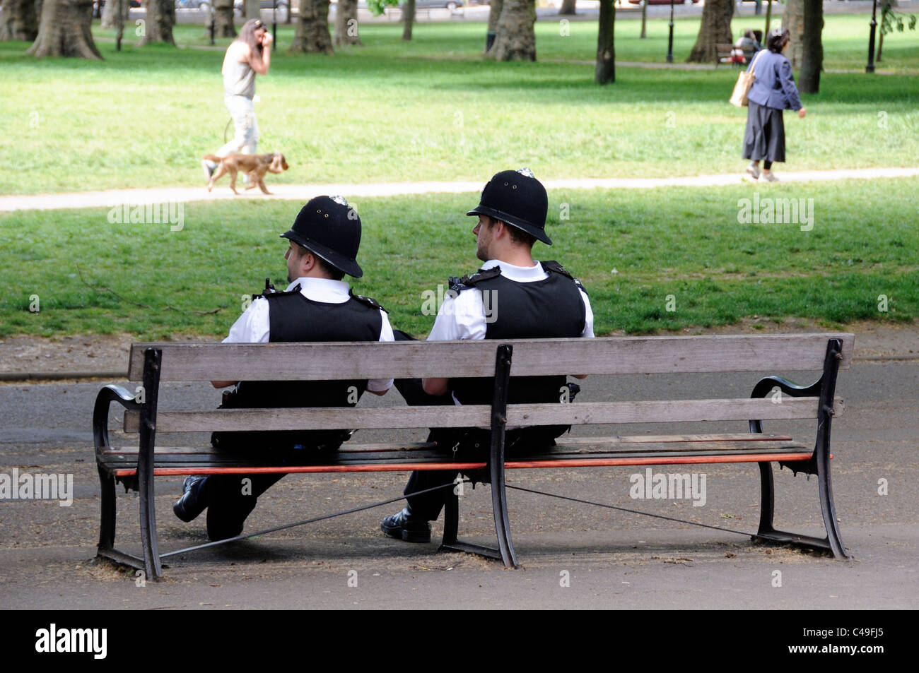 Bobbies sitting on a bench, two Metropolitan police officers watching activities on Highbury Fields in summer London - Stock Image