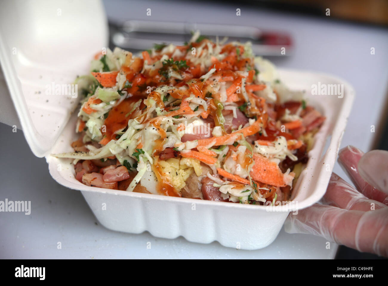 baked potato under salad and bacon in polystyrene packaging box - Stock Image