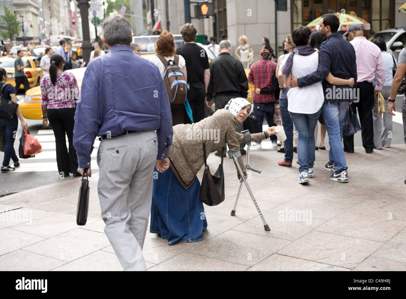 Disabled gypsy woman begging on 5th Avenue in New York City. - Stock Image