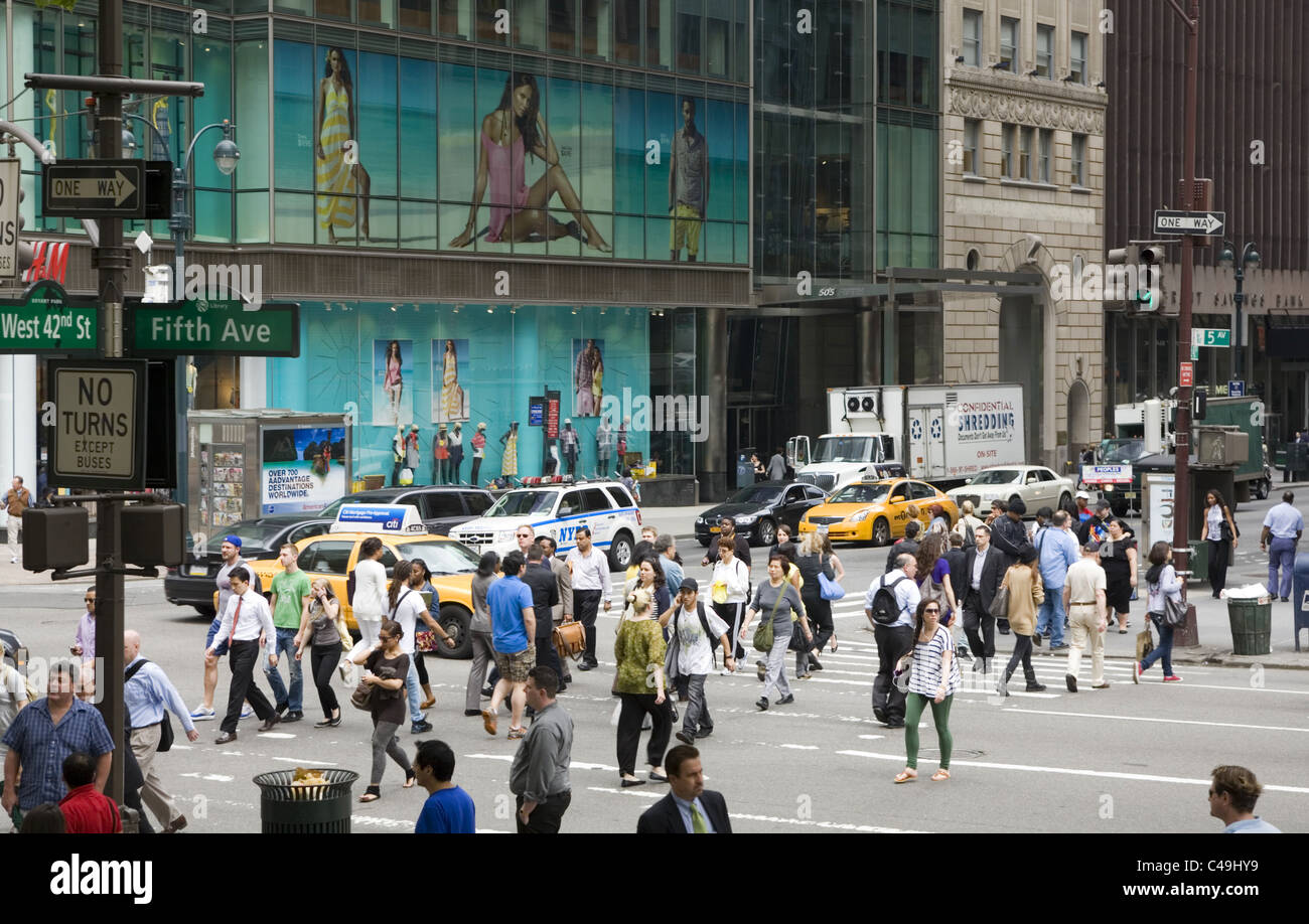 The always busy street corner of 5th Avenue and 42nd Street in New York City. - Stock Image