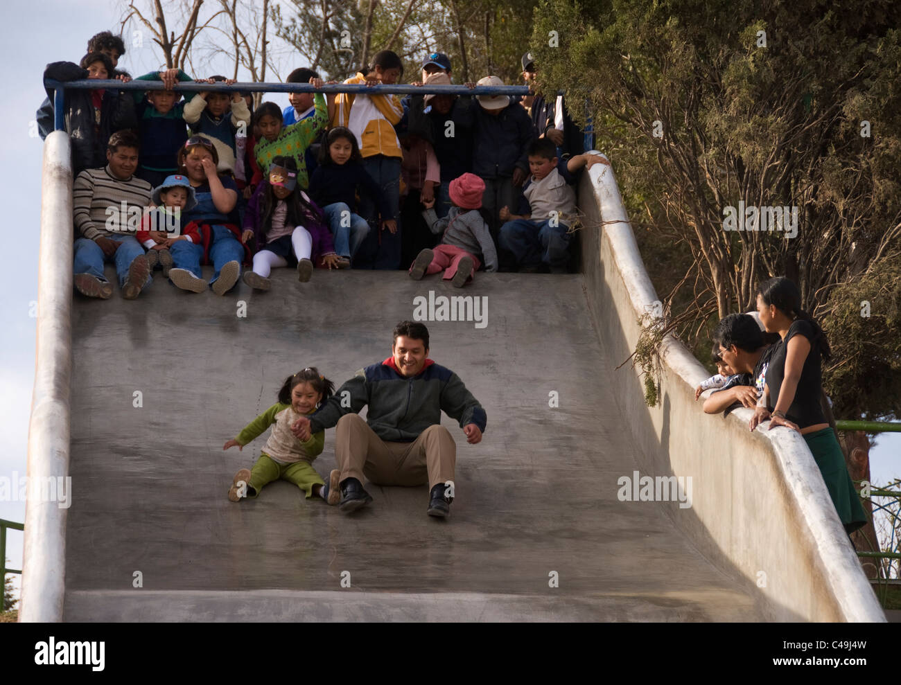 La Paz, Miraflores, children's playground, man and young girl on giant slide. - Stock Image