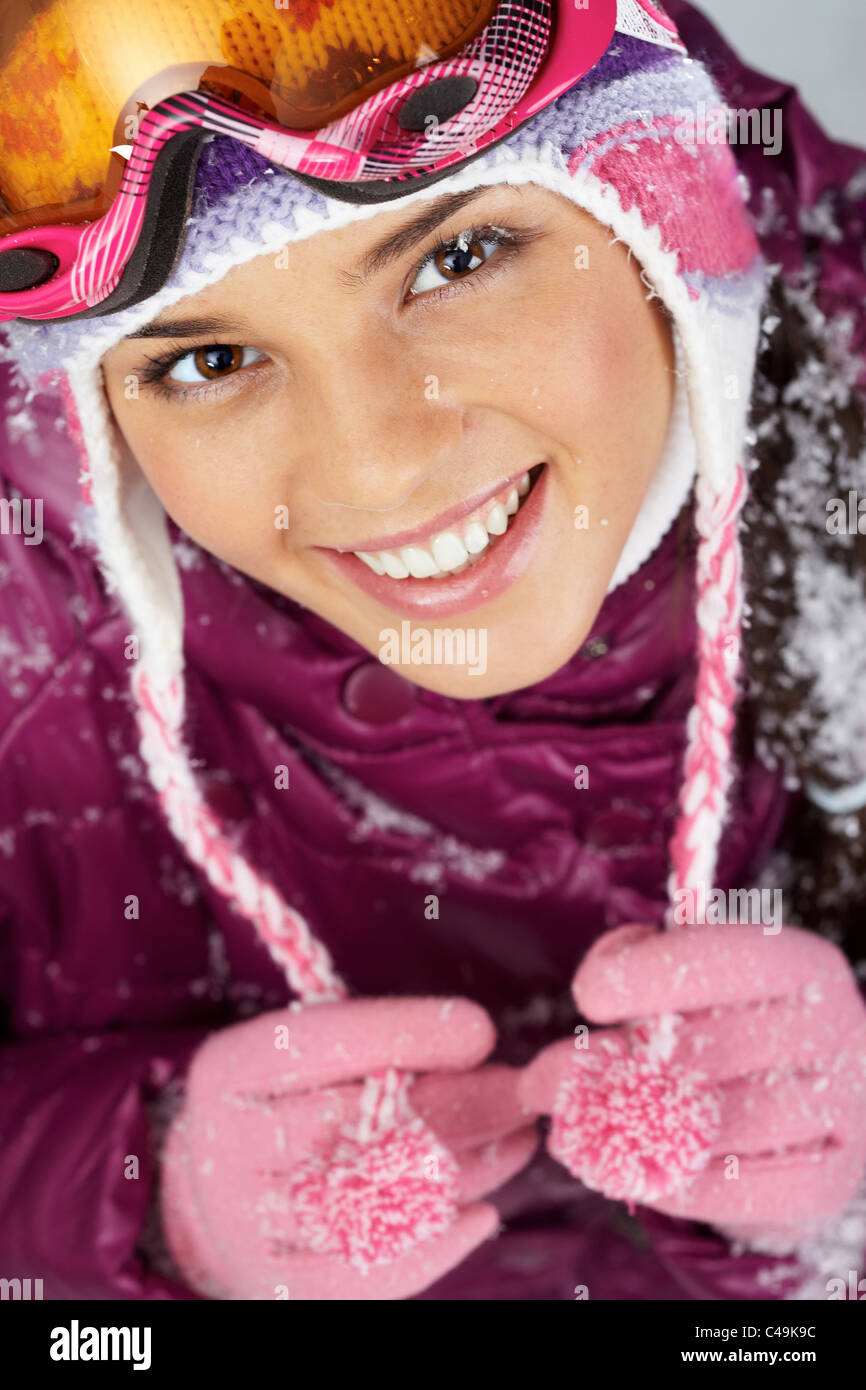 Pretty woman in goggles and winter clothes looking at camera with smile Stock Photo