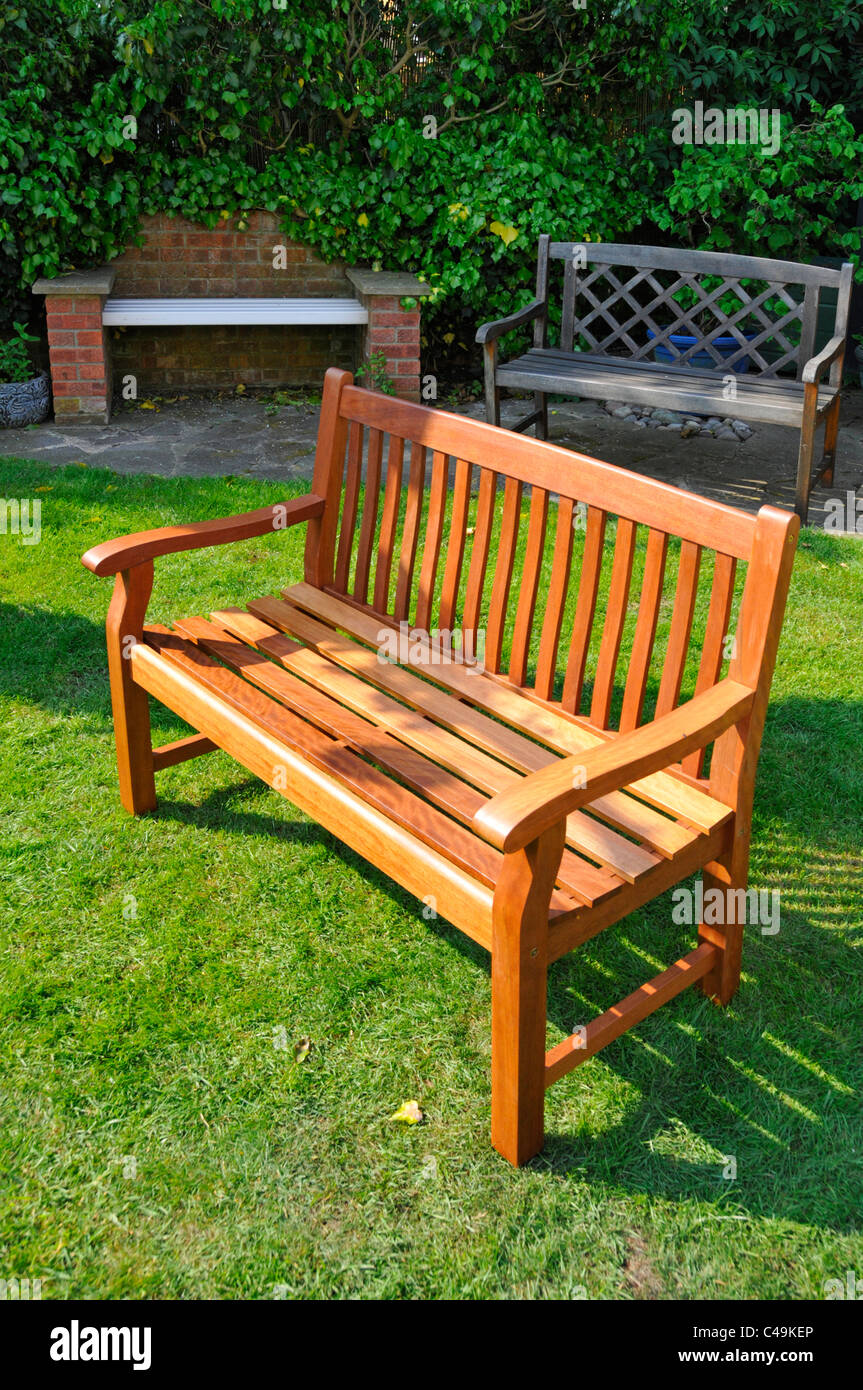 New self assembled pre treated flat pack timber DIY do it yourself garden seat with similar weathered aging wood Stock Photo