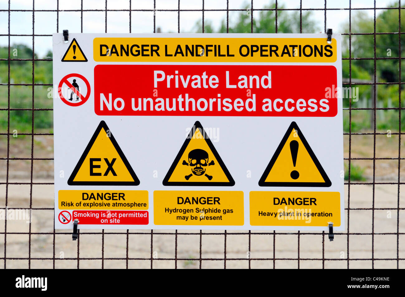 Warning sign landfill site private land danger from explosion so no smoking Hydrogen Sulphide gas & heavy machines - Stock Image