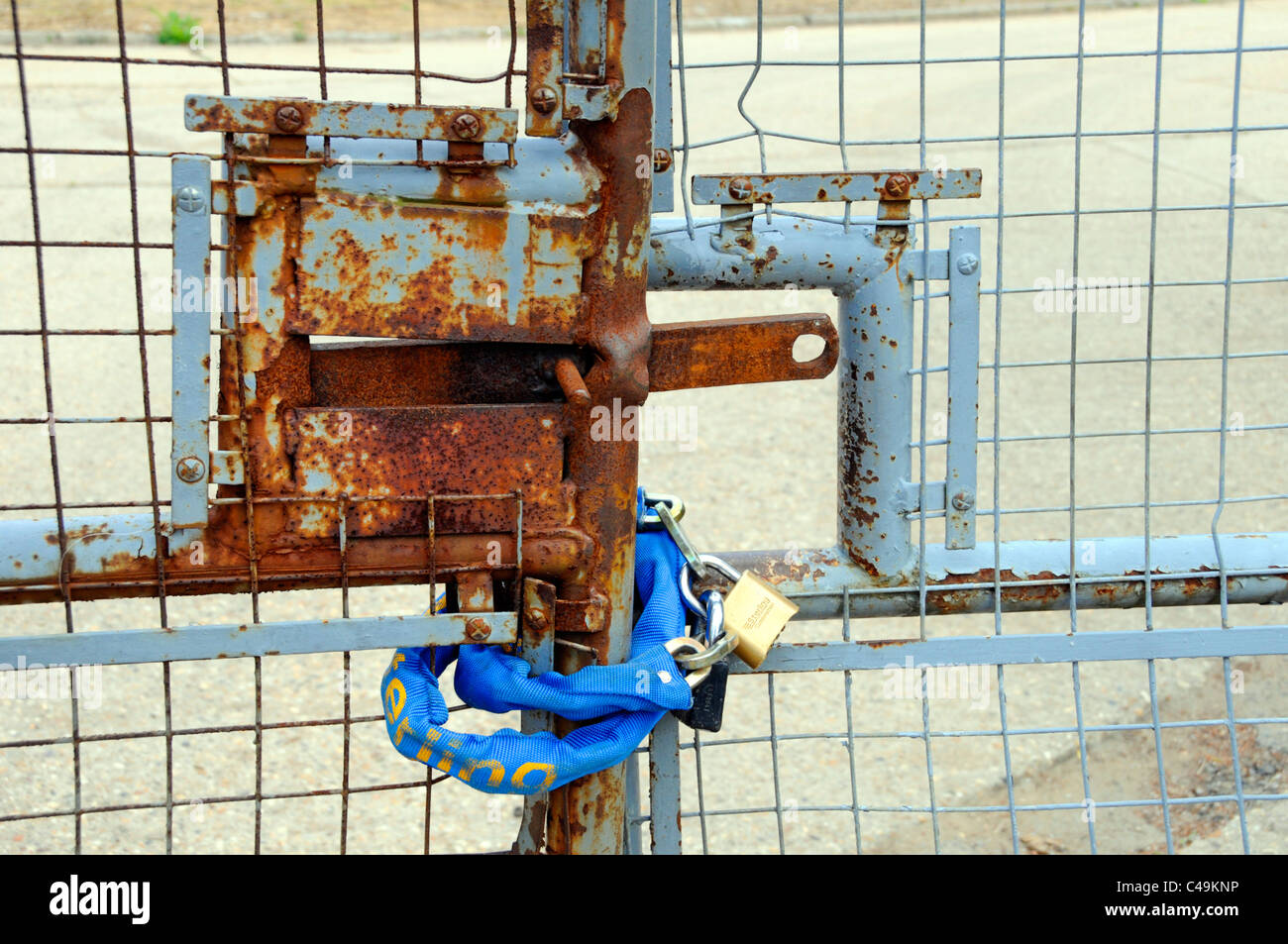 Padlock and chain around entrance gates to disused premises concept image for subjects including redundancy closure - Stock Image