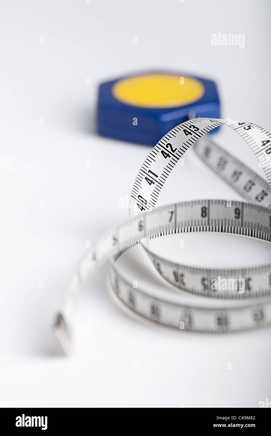 close up of a tape measure rolled on white background - Stock Image