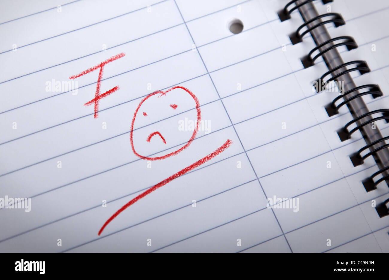 F grade and a sad smilie, written in red letters in a spiral pad, shallow DOF - Stock Image