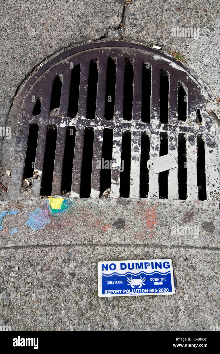 No dumping only rain down the drain sign on San Francisco street next to drain cover with paint splashes - Stock Image