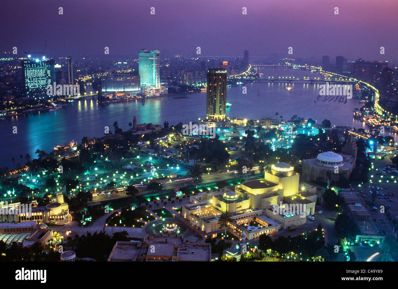 Egypt, Cairo, City by Nile river with Opera House in foreground at dusk - Stock Image