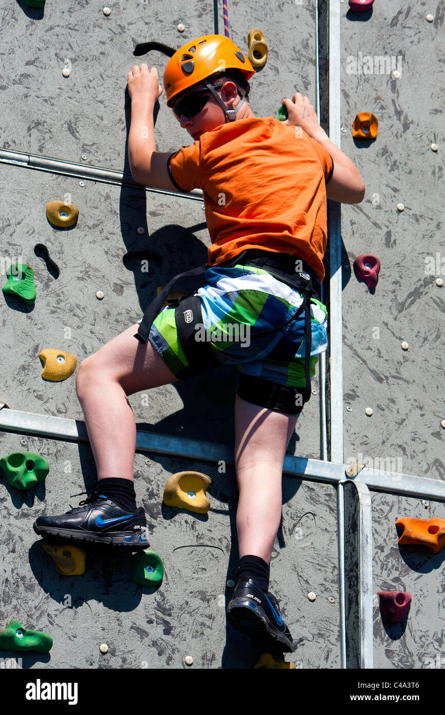 a young boy on a practice climbing wall C4A3T6 boy child harness scared stock photos & boy child harness scared
