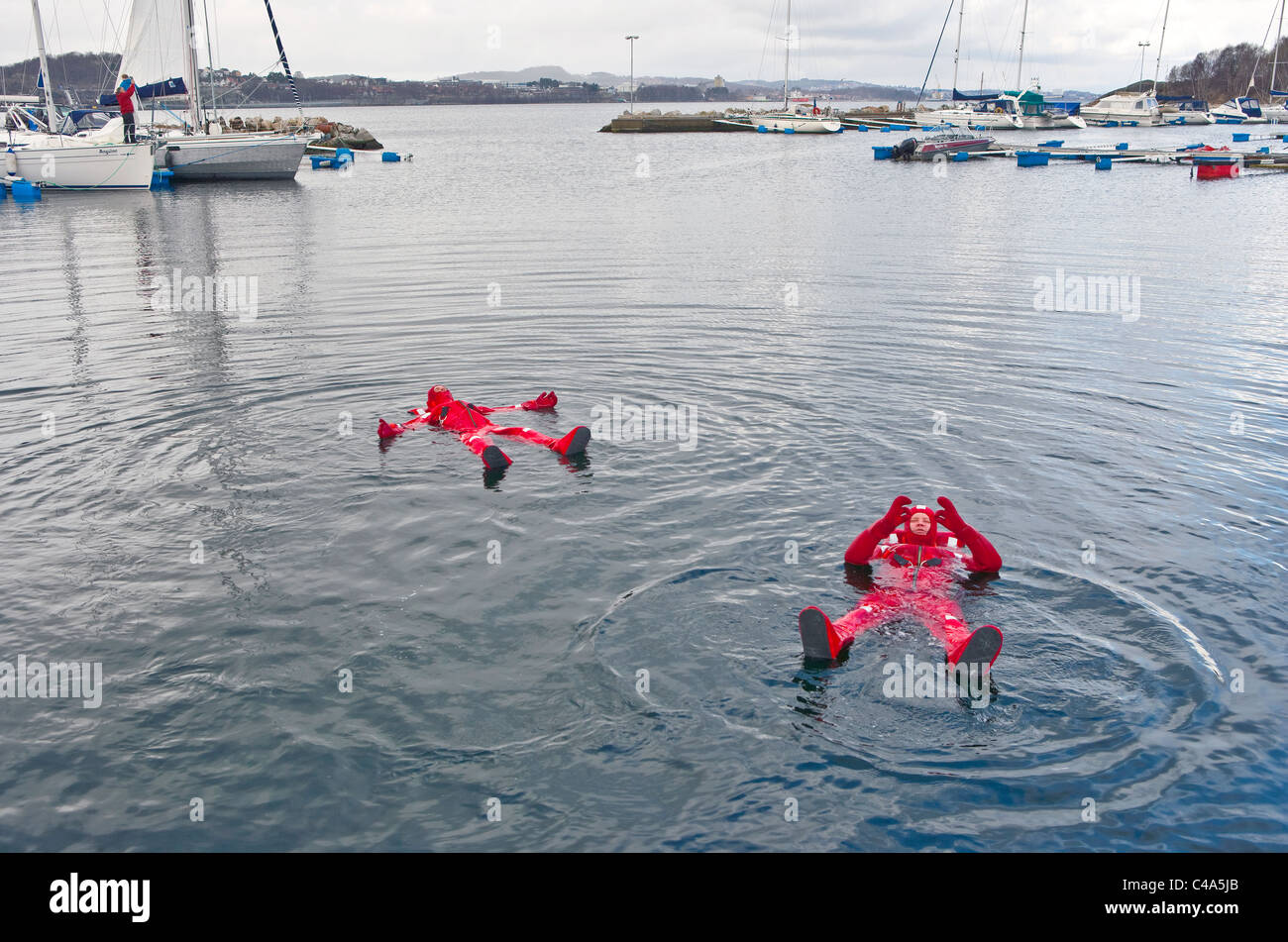 Sailors try out survival suits. - Stock Image