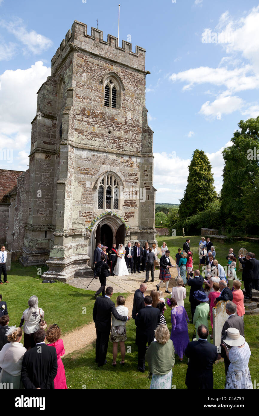 wedding guests and family watching bride and groom outside St Mary & Cuthberga & All Saints Church Witchampton - Stock Image