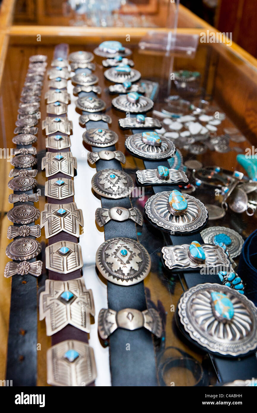 Native American turquoise and silver Jewelry on display in a Trading Post.  Concha belts, mainly Navajo. - Stock Image