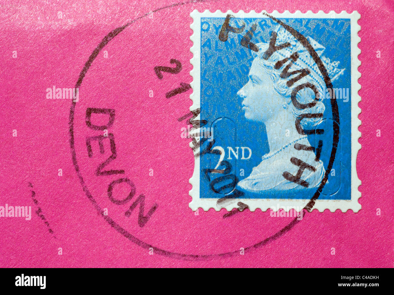 A Second Class (2nd) light blue Royal Mail Post Office Postage Stamp with HRH Queen Elizabeth II head on pink envelope - Stock Image