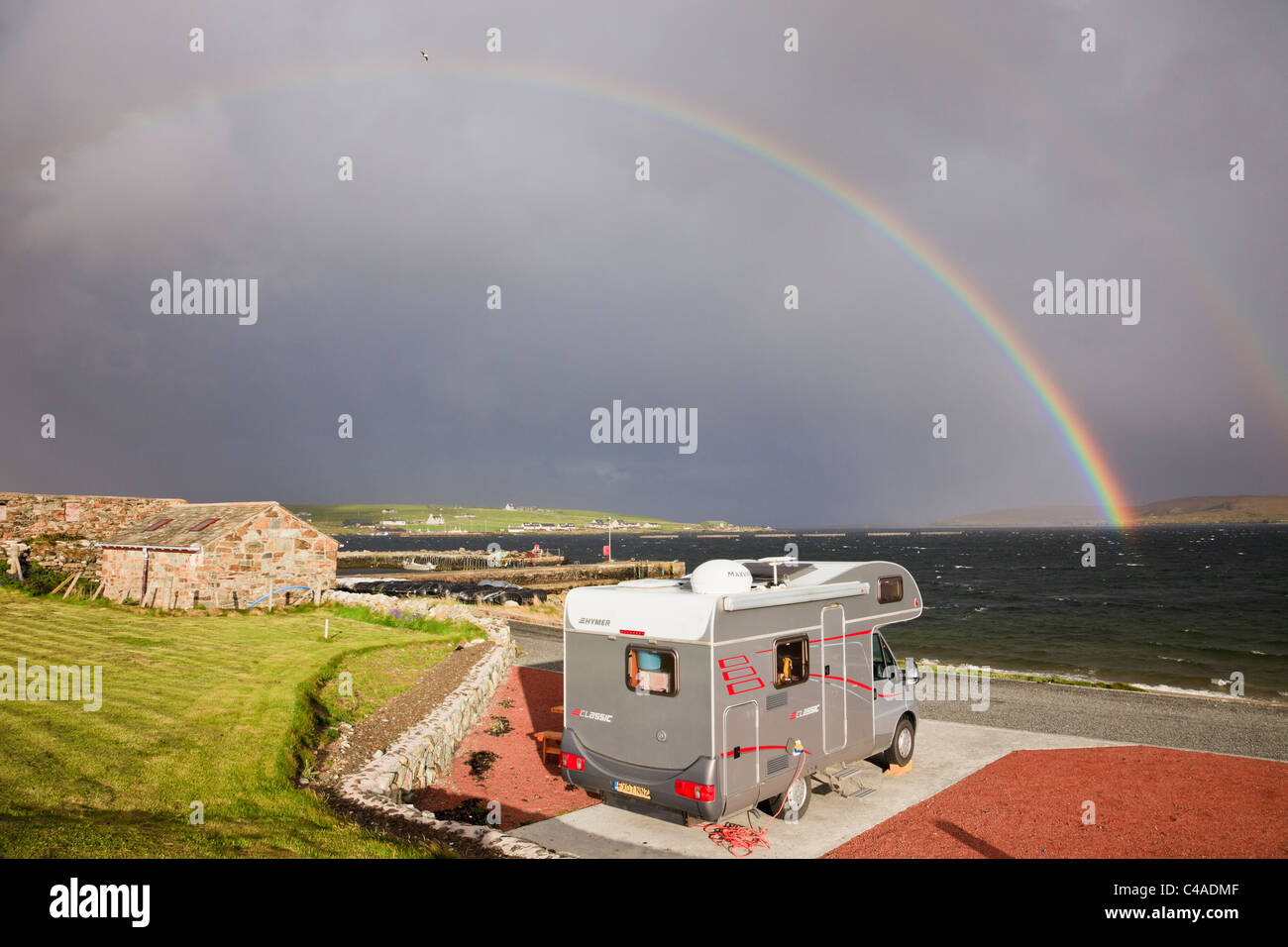Motorhome in Gardiesfauld youth hostel campsite with rainbow and dark clouds. Uyeasound, Isle of Unst, Shetland - Stock Image
