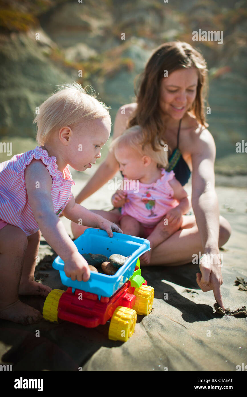 Mother Playing with one year old Identical Twin girls at the Beach - Stock Image