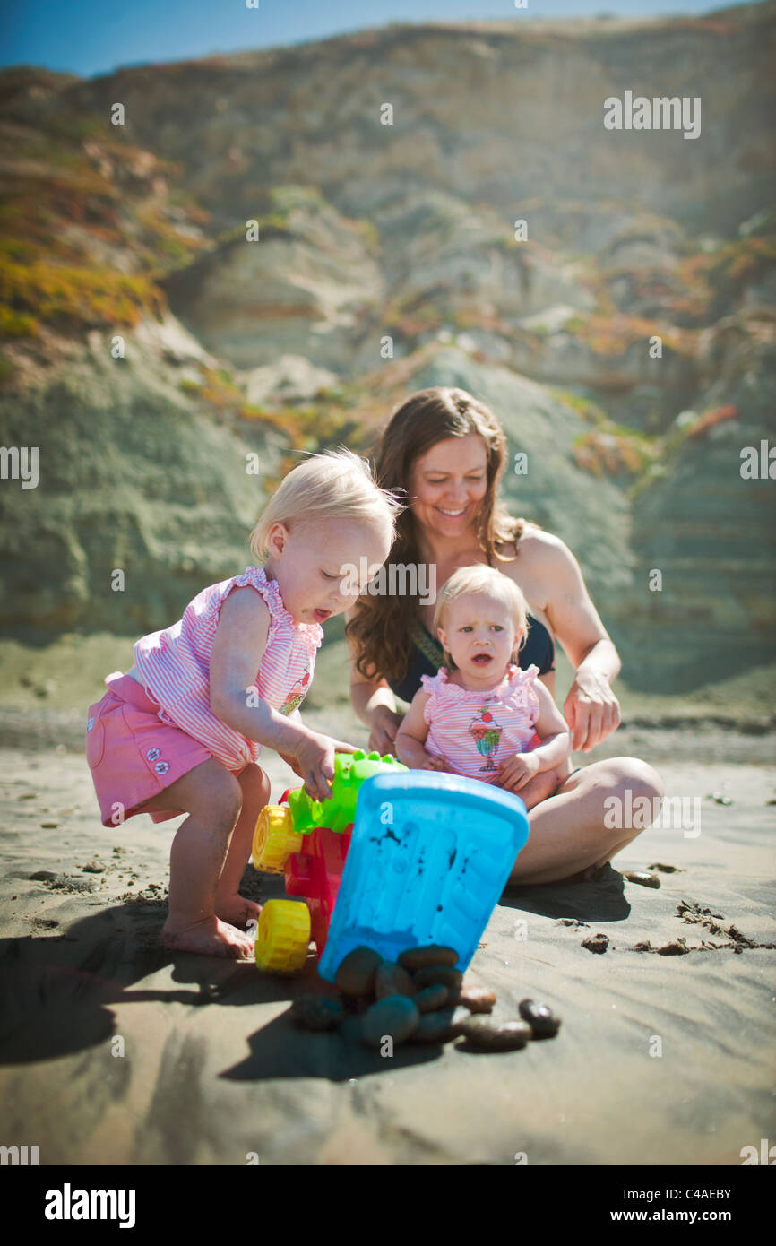 Mother and 1 Year Old Twin Girls Playing on the Beach - Stock Image