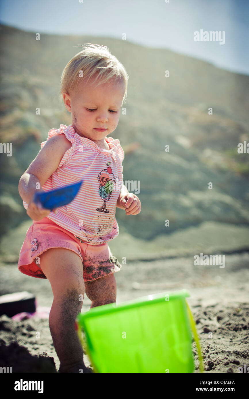 I Year Old Girl at Beach Playing with Sand Toys - Stock Image