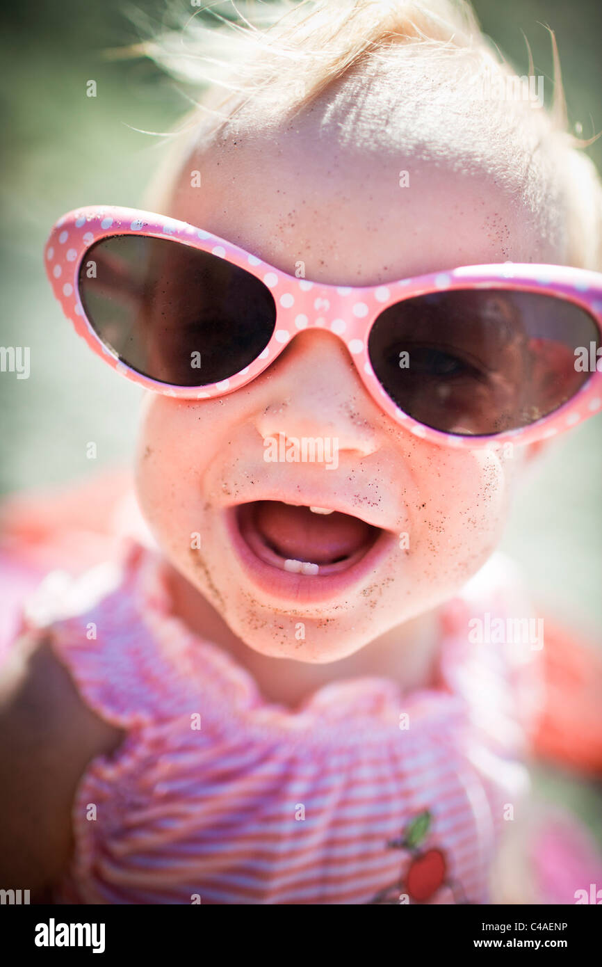 Toddler Girl Wearing Big Sunglasses at the Beach - Stock Image