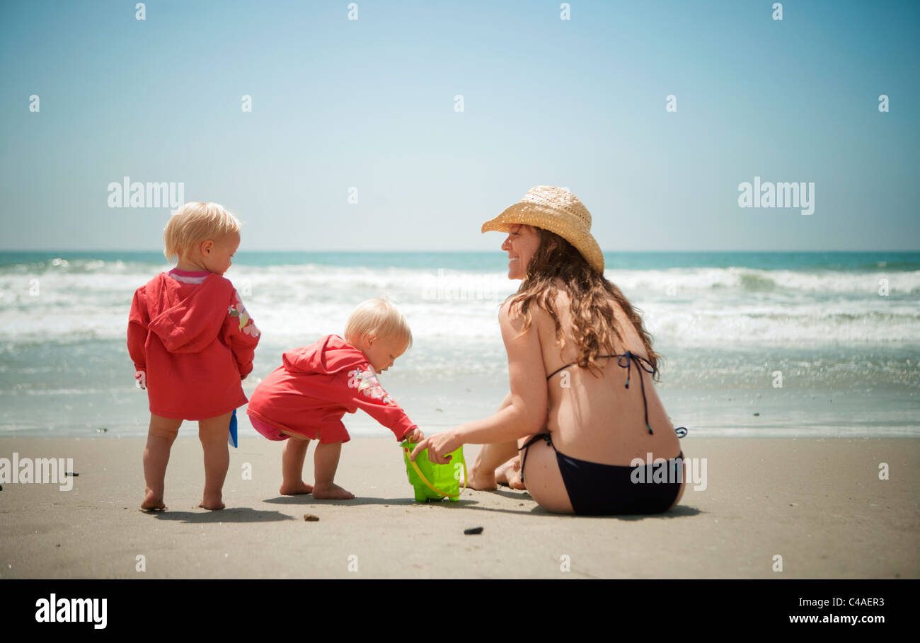 Mother at Beach with Twin Daughters - Stock Image