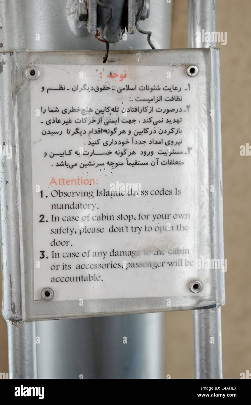 A sign in the ski telecabin at Dizin ski resort Iran informing people of the need to observe Islamic dress code - Stock Image