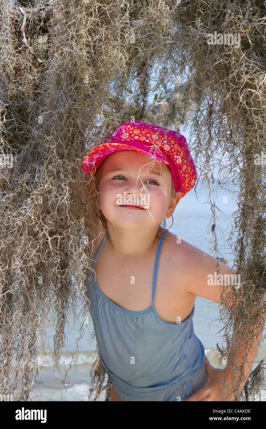 6-years girl with the spanish moss at the ocean beach. - Stock Image