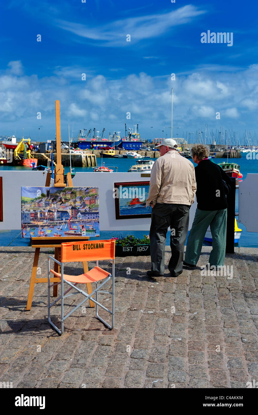 a couple looking at the artist bill stockman's paintings of brixham harbour devon england uk - Stock Image