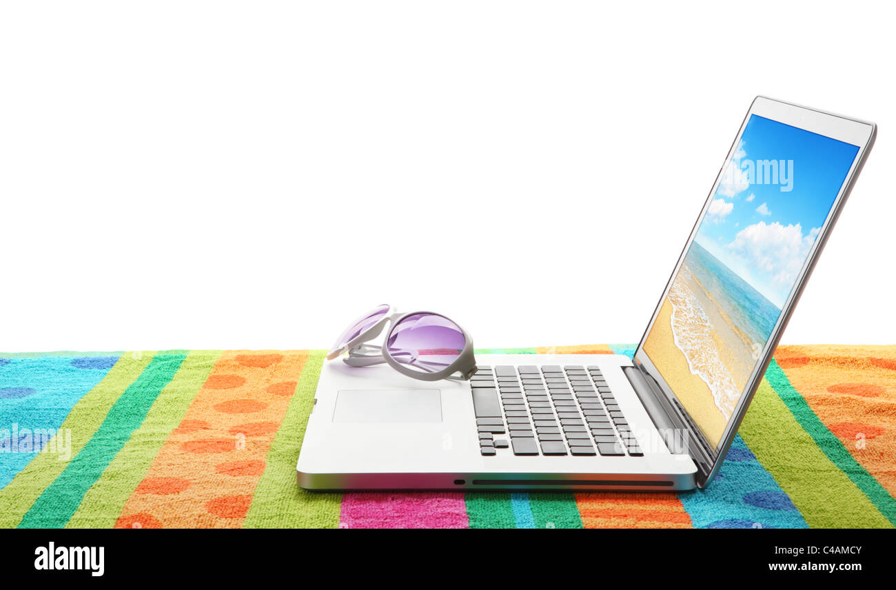 Laptop computer with sun glasses on beach towel.The photo on laptop is mine. - Stock Image