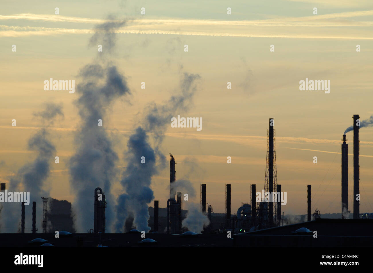 Smokes and chimneys at sunrise of industrial Total petrochemicals platform, Carling Saint Avold, Moselle, Lorraine, - Stock Image