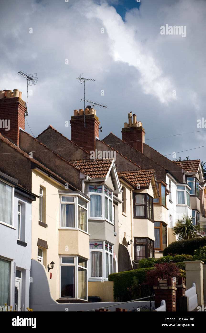 Stormy clouds over terraced housing with storm clouds looming,In architecture and city planning, a terrace(d), row - Stock Image