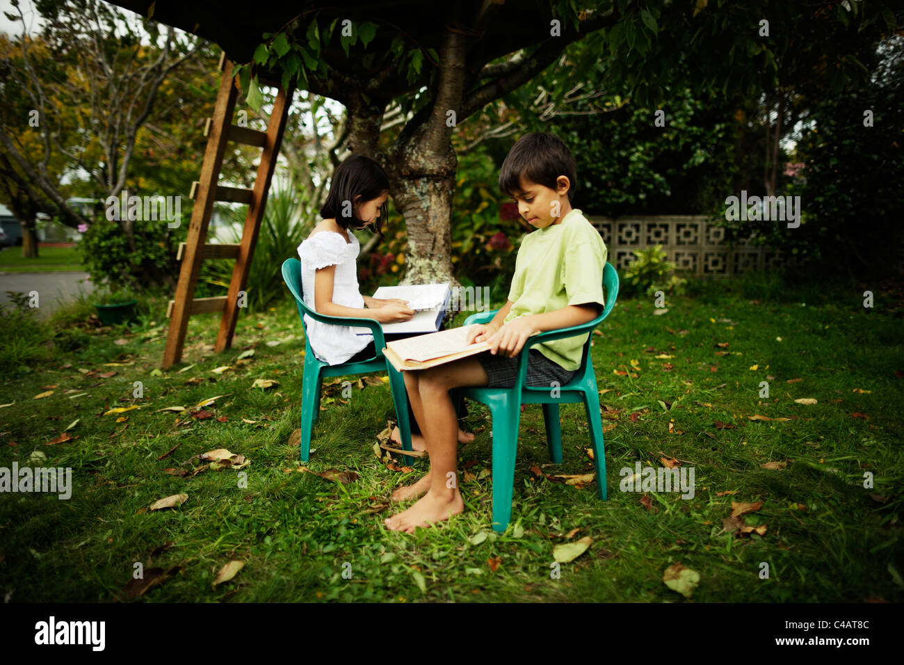 Boy and girl sit in plastic chairs reading books in garden underneath treehouse. - Stock Image