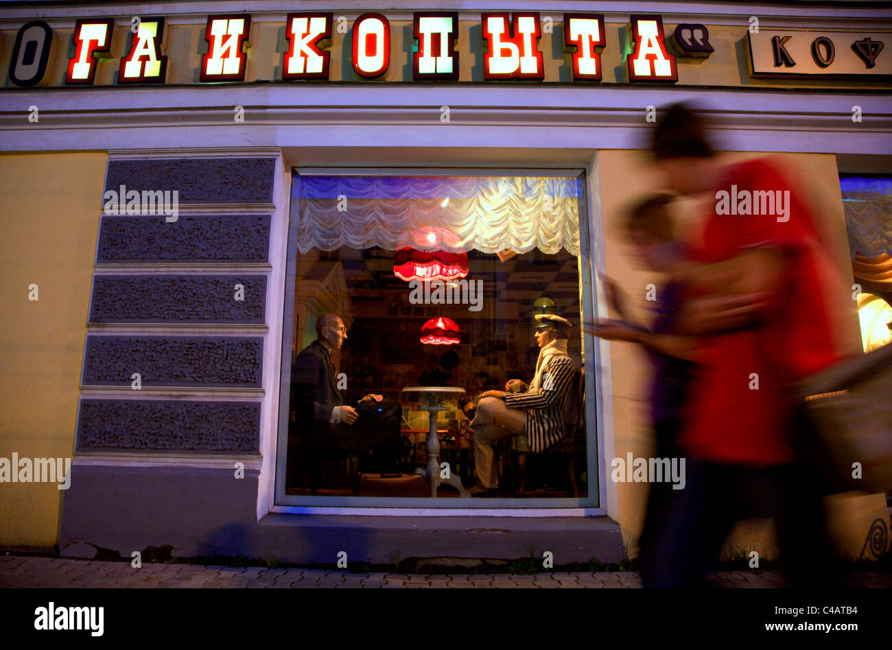 Russia, Golden Ring, Kostroma; Youths walking along the streets in town in front of a stylish restaurant Stock Photo