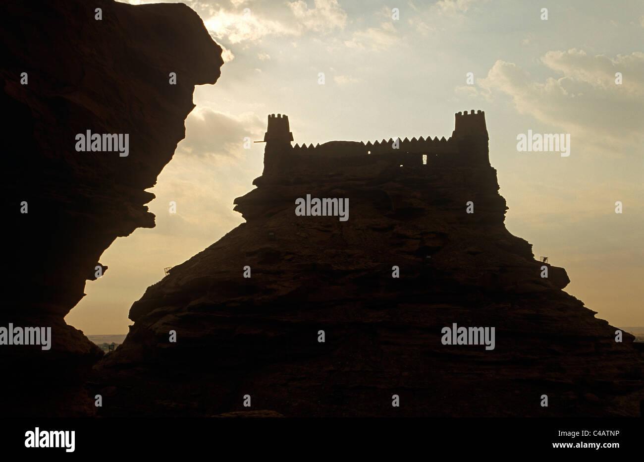 Saudi Arabia, Jouf, Sakaka. Brilliant sunshine silhouettes the brooding outline of the 19th-century Zaabel Fort, Stock Photo