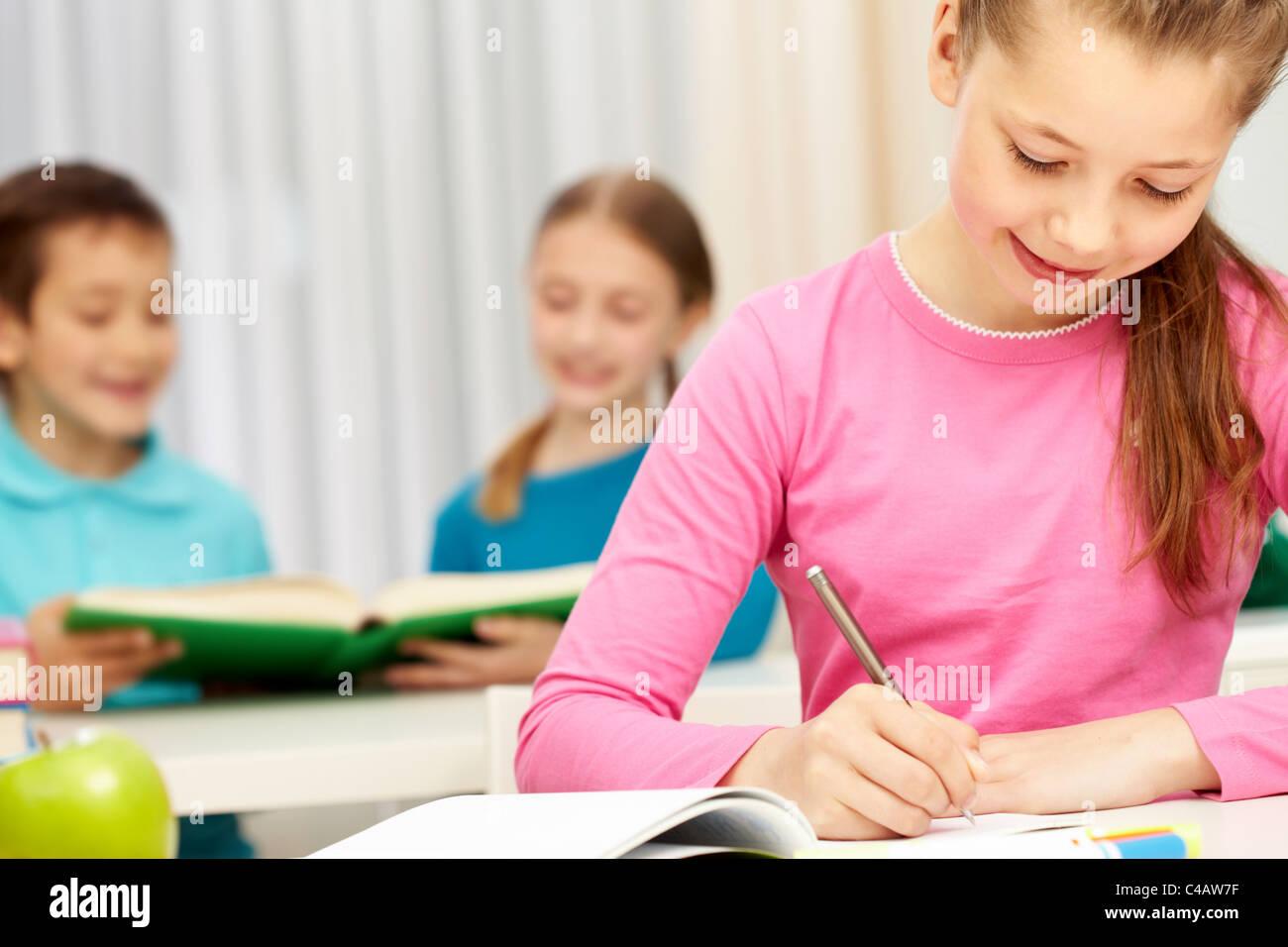 Portrait of smart schoolgirl making notes in her exercise book - Stock Image