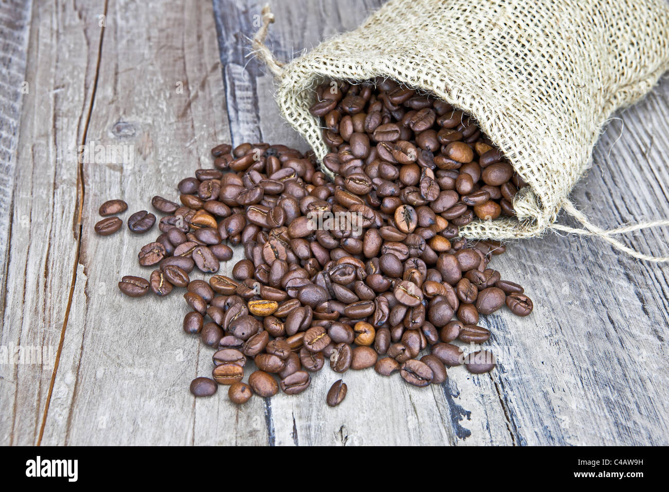 Coffee beans in a jute bag on a wooden table - Stock Image