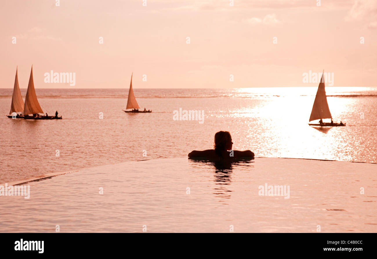 Zanzibar, Matemwe Bungalows. A tourist stands at the edge of an infinity pool watching the Dhows. MR. Stock Photo