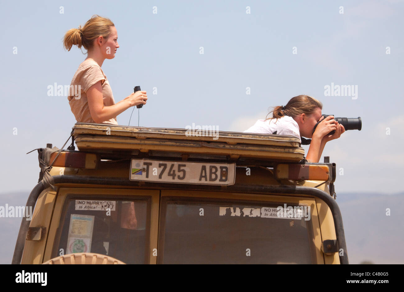 Tanzania, Ngorongoro. Two women look out from a safari vehicle at wildlife. - Stock Image