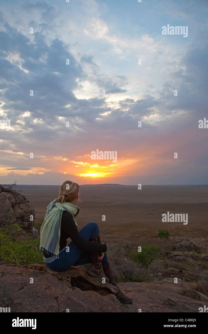 Tanzania, Olduvai. A tourist enjoys the sunset looking out over the plains towards the Serengeti. MR. Stock Photo