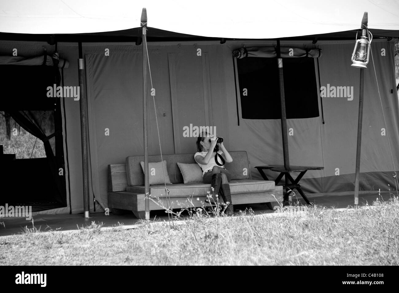 Tanzania, Serengeti. A guest looks out over the plains from the comfort of her tent at Lemala Ewanjan. MR. Stock Photo