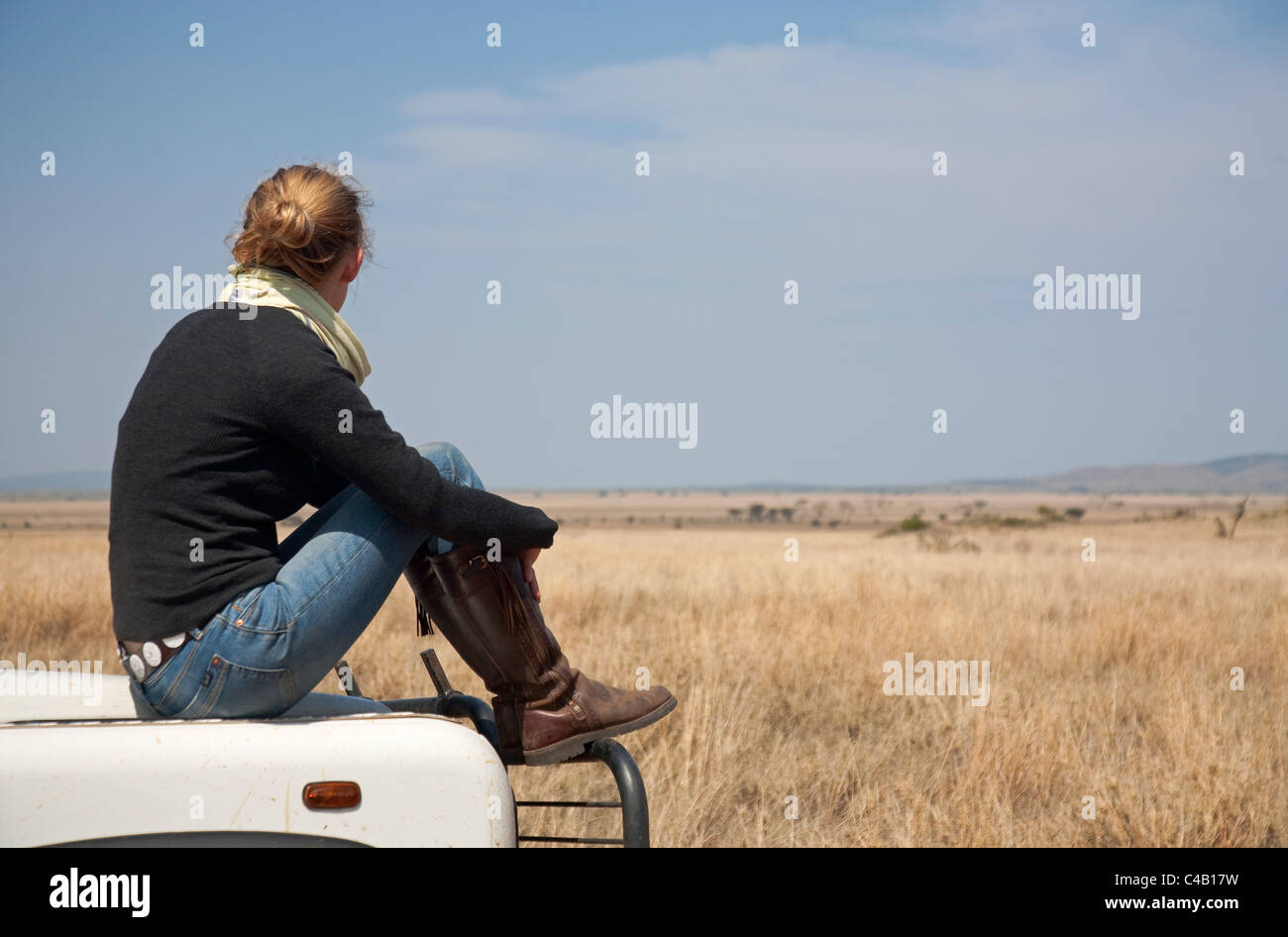 Tanzania, Serengeti. A woman looks out over the Serengeti plains from the bonnet of her Land Rover. MR. Stock Photo