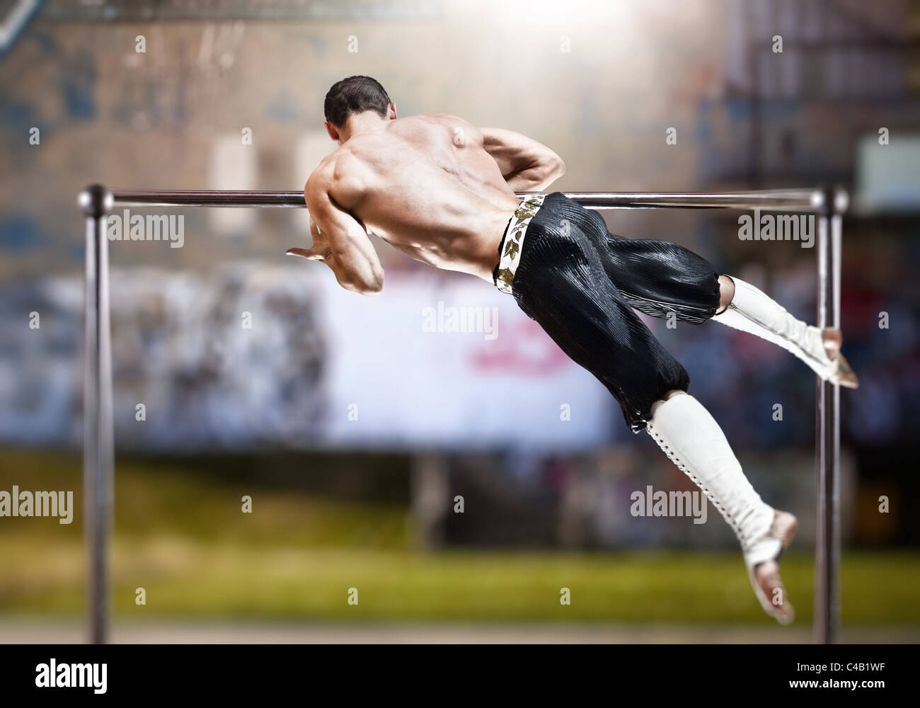 Young man doing sports exercises outdoors. - Stock Image
