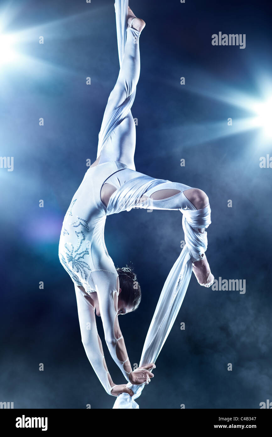 Young woman gymnast. On black background with flash effect. - Stock Image