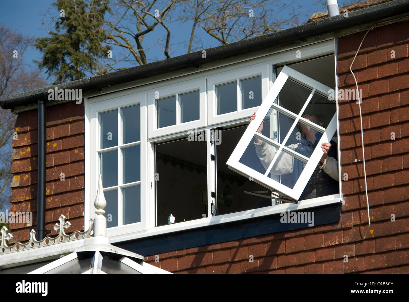 Installing A rated energy efficient replacement double glazed windows on an old house - Stock Image