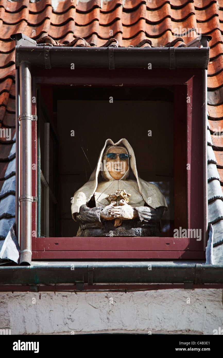 A mannequin nun stands in the dormwer window of a house in Brugge Sint Kruis, Brugge (Bruges), Belgium - Stock Image