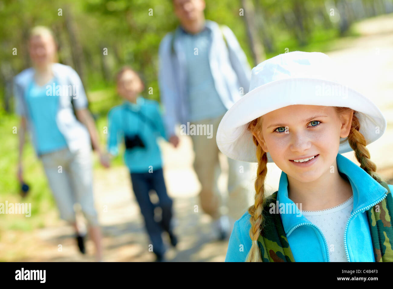Portrait of pretty girl looking at camera with her family on background in summer - Stock Image